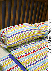 Bed - bedroom interiors - Colorful bed linen on a wooden bed