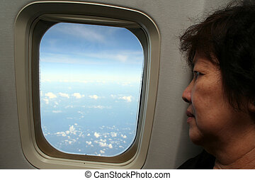 Airplane Passenger - An elderly asian woman looking through...
