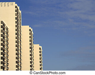 yellow condominium building at sunset against blue sky -...