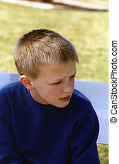 Attentive - Boy sitting on a park bench, in profile.