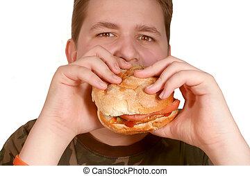 eating hamburger - young teenage boy eating hamburger