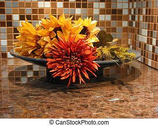 Ktchen decoration - Artificial flowers in a bowl on granite...