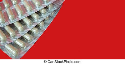 Capsules - Pack of capsules isolated on red background, with...