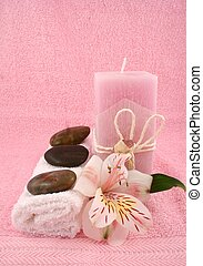 Massage Therapy - A pink candle, some towels, a facecloth,...