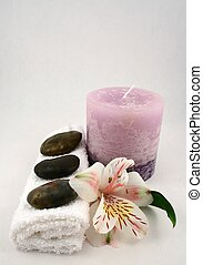 Massage Therapy - A purple candle, some stones, towels and a...