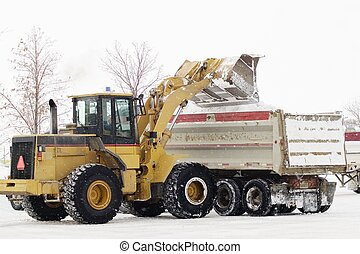 Snow Removal - A tractor loads snow into a truck for...