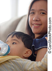 Baby drinking bottle while sitting on mom\\\'s lap