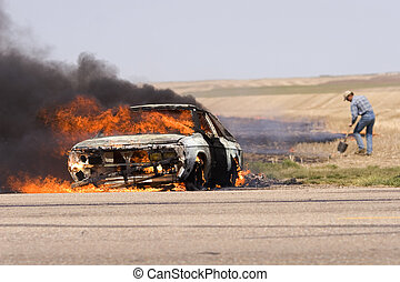 Out of control - Car fire with a man trying to stop a grass...