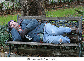 Homeless Man On Bench - Full View - A full view of a...
