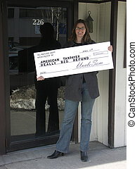 Big Refund - Smiling woman holding an oversize tax refund...