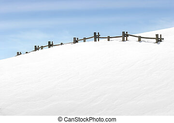 fence on snowy hill with blue sky