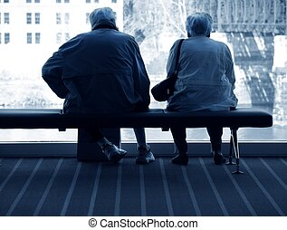 Together - elderly couple sitting together on bench in front...