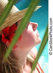 Tropical Sunbather - Woman sunbathing behind tropical...