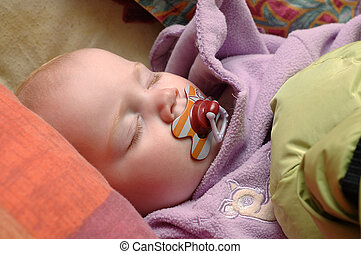 Sleeping baby girl with pacifier dummy in mouth