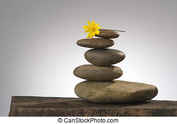 balance and beauty - balancing river rocks with daisy on top