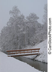 Snow Bridge - Snow covered landscape with bridge and trees.