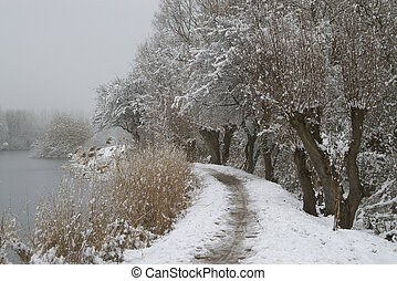 Snow landscape near river - Snow covered trail besides the...