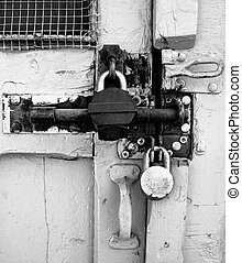 Two Locks B&W - Two padlocks and a bolt securing a shed...