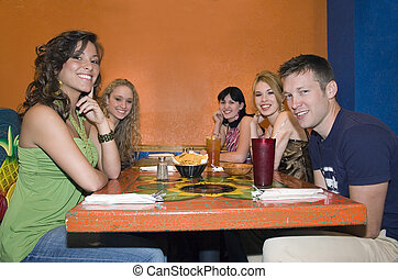 Friends Restaurant - Group of college students sitting at...