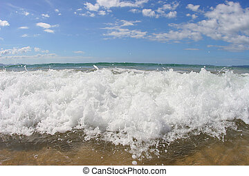 breaking wave - a wave breaking on the beach - closeup shot