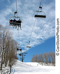 Downhill ski chairlift on a ski resort on bright sunny day