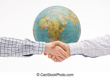 Globalisation - Two hands shaking under a flying globe -...