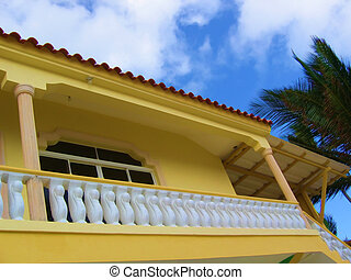 Yellow House - Bright yellow house set against blue sky with...