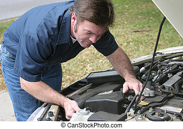 Auto Mechanic Checks Engine - An auto mechanic checking the...