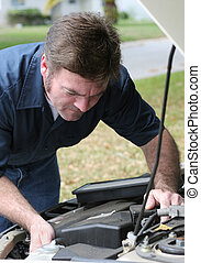 Mechanic Under Hood - An auto mechanic looking under the...