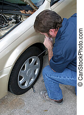 Removing Hubcap - A mechanic removing the hubcap from a car...