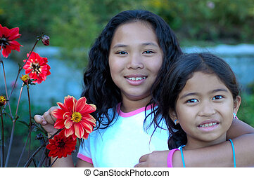 Sisters - Two siblings pose while playing in the garden