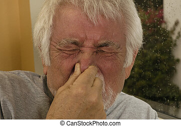 Man Sneezing - Older man holding nose sneezing.