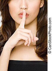 Finger on Lips - A beautiful woman holds her finger up to...