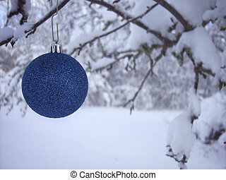 Blue Christmas Ornament hanging outside on snow covered...