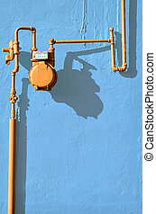 The Orange Meter - An orange gas meter against a blue wall