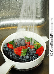 Washing berries - Blueberries and strawberries being washed...