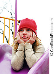 Girl on playground thinking - Young girl in a red hat on...