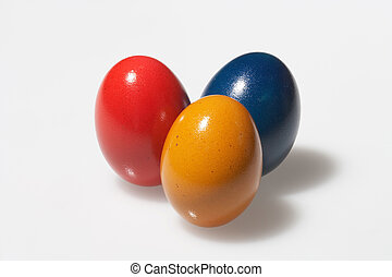 yellow, red and blue - three easter eggs on white background...
