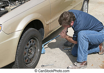 Mechanic Using Jack - A mechanic using a jack to lift a car...