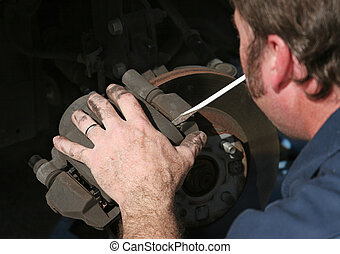 Removing Brake Housing - An auto mechanic removing the brake...