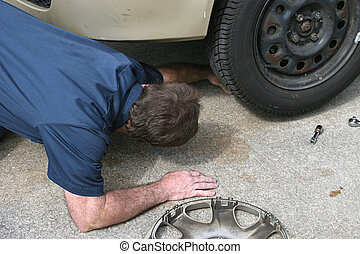 Mechanic  - A mechanic looking underneath a car.