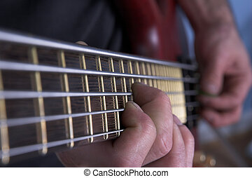 bass guitar neck - Closeup of five string bass guitar being...