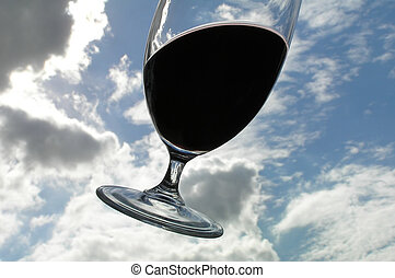 Floating glass with red wine against sky with clouds