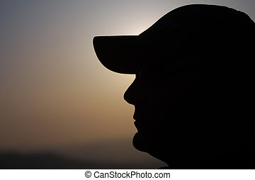 man with cap silhouete at sunrise