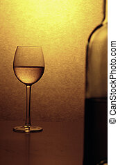 wine glass in reduced colours; in front an unsharp wine...