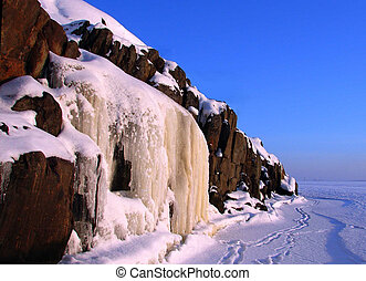 Ice waterfall, rock and blue sky