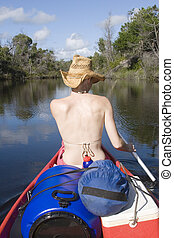 woman canoing from behind portrait - woman canoing down...