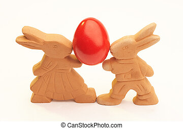 easter - two ceramic easter bunnys carrying one red easter...