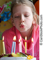Happy birthday - Young girl blowing birthday candles