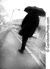 dark man - a darm man walking down the street carrying an...